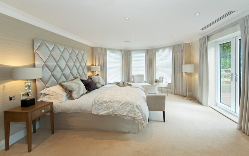 Large windows wrap this white toned bedroom, spiked with a massive button tufted headboard at left. A set of white framed French doors to the right allow for direct patio access and plentiful natural light.