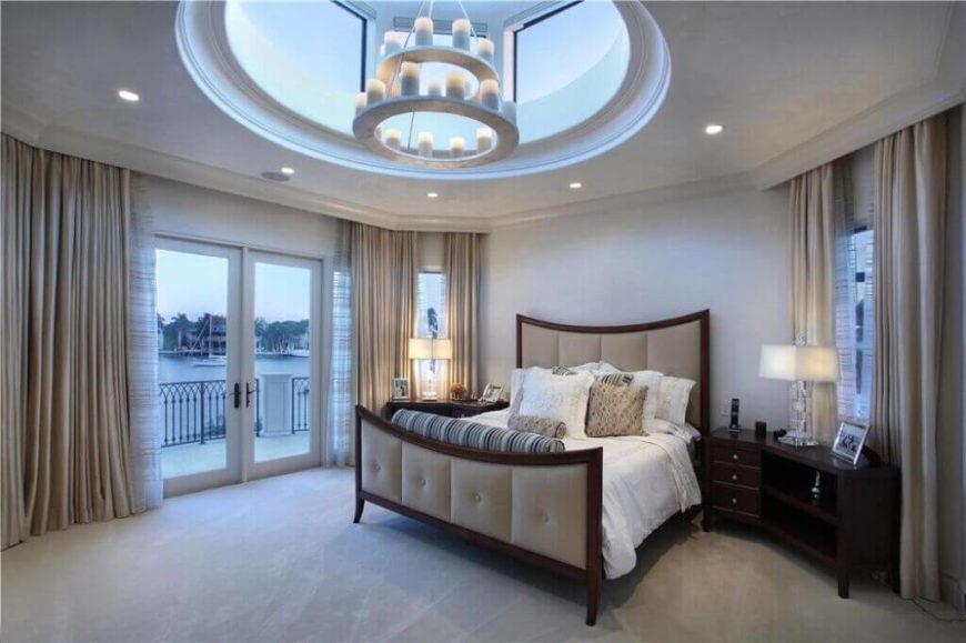 A unique skylight feature in this room raises its level of sophistication and surprise, with a candle-style chandelier hanging in the void. The room features a pair of glass French doors with balcony views over a nearby lake.