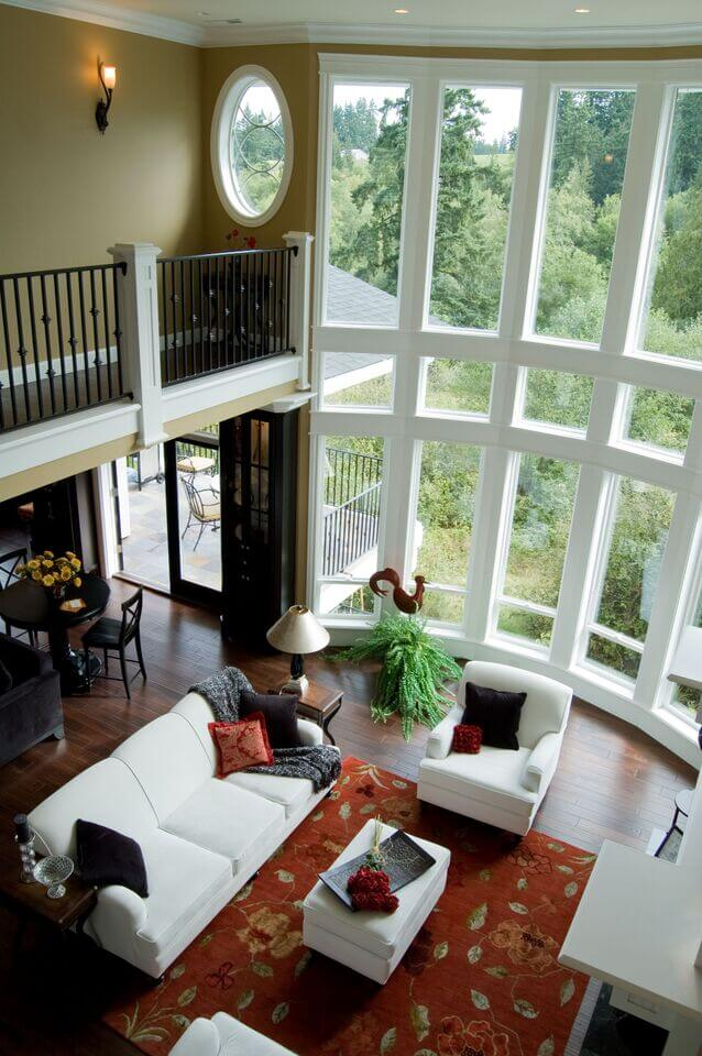 Looking down into this vast, open-plan living room we see a matching set of white furniture orbiting a floral area rug over hardwood flooring. White walls frame the massive set of two-story windows.