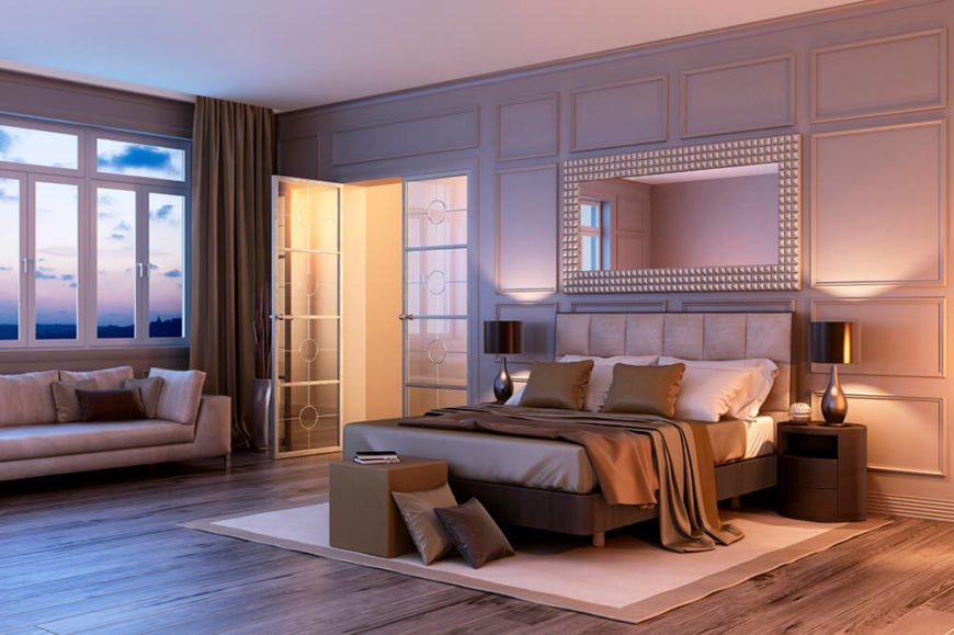 Elegant wainscoting wraps this contemporary bedroom over a right hardwood floor. A large set of windows allows for expansive views, while a pair of glass French doors provide access to the rest of the en suite.