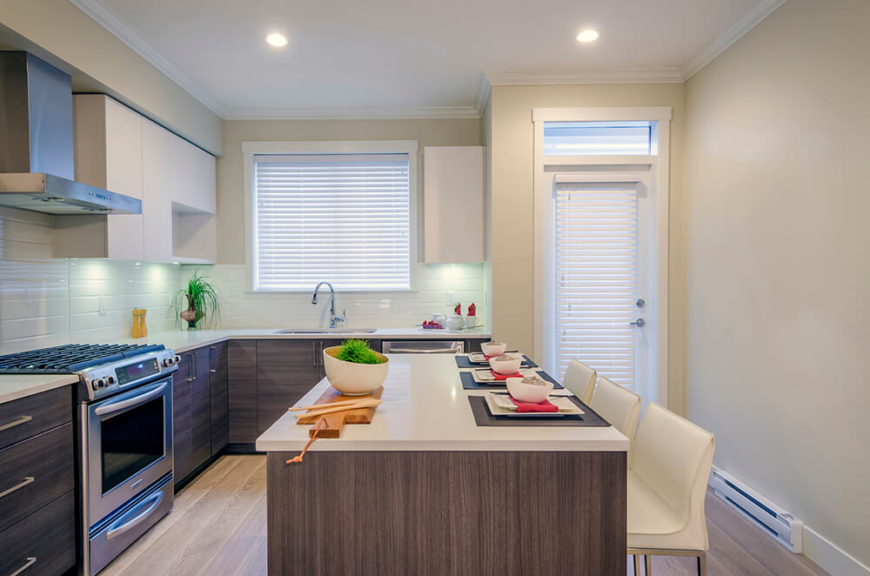 Cream colored chairs match the countertops and the upper cabinets while weathered wood makes up the bottom in the modern-contemporary kitchen. Splashes of red and bright green bring more, simple color into the space to spice it up.