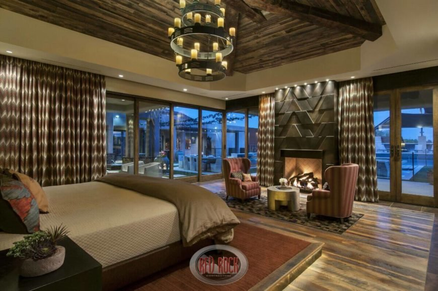 This rustic luxury bedroom features wraparound glazing for the ultimate in open style, with a pair of wingback chairs standing next to a fireplace at center. French doors comprise part of the glass enclosure.