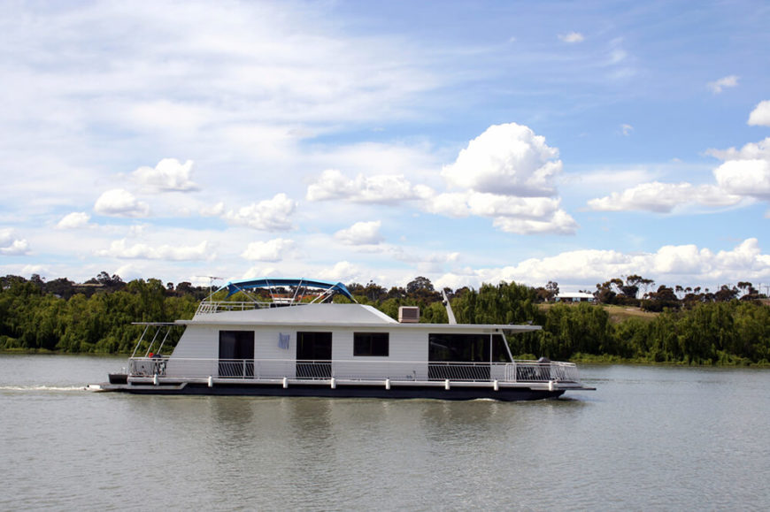 A large leisure houseboat designed to troll along the quiet lakes of North America. This is a large craft that is almost entirely cabin, with a perimeter of balustrade around the exterior and a large covered deck on top.