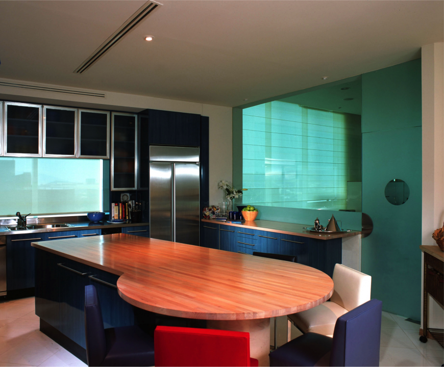 Color is a key component in to this kitchen design. Navy blue cabinets is complemented by the frosted blue glass of the accent wall. The natural wood counter tops break up the dark colors of the room and more pops of color are added in the leather accent chairs placed around the end of the island.