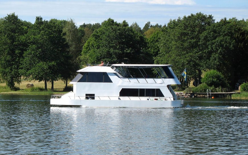 A large, sleek white houseboat with a two-story glass-wrapped cabin, meaning that even when the owners retreat inside to escape the sun, they still have a magnificent view.