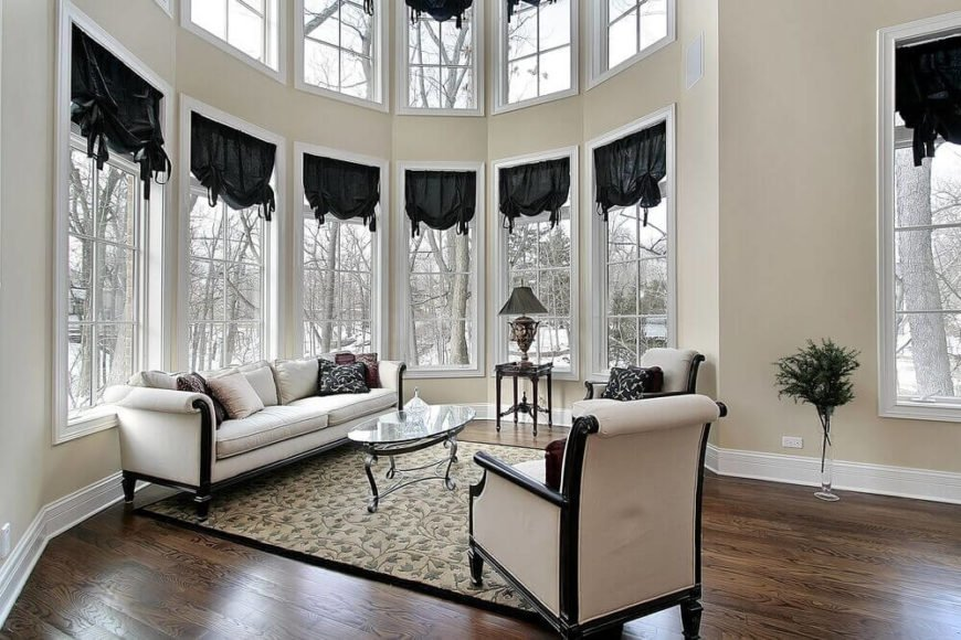 This living room features a full two stories of wraparound windows with small black drapes for a dramatic, high contrast look. The white and dark wood framed furniture set mirrors this elegant aesthetic.