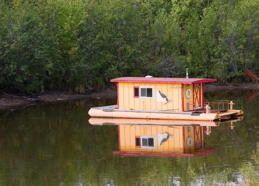 """A more rustic """"shanty"""" houseboat. Shanty boats are small homes floating on rafts, which distinguishes them from houseboats. This shanty boat is brightly colored"""