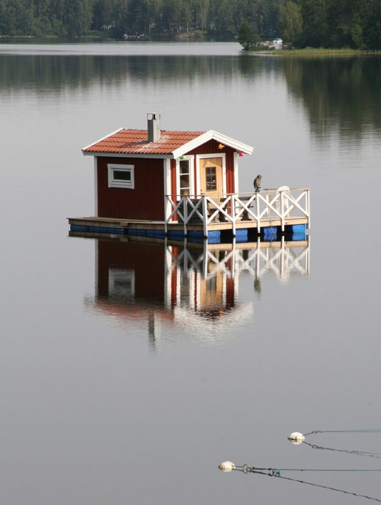 Another shanty boat with a small shed-sized home on the deck and a fenced off area on the front with a small opening for mooring for a smaller boat.