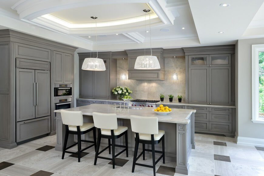 A beautiful white and gray kitchen with lovely crystal shades over the pendant lights hanging from the slightly off-center tray ceiling. A textured backsplash contrasts gorgeously with the pattern of the tile flooring.