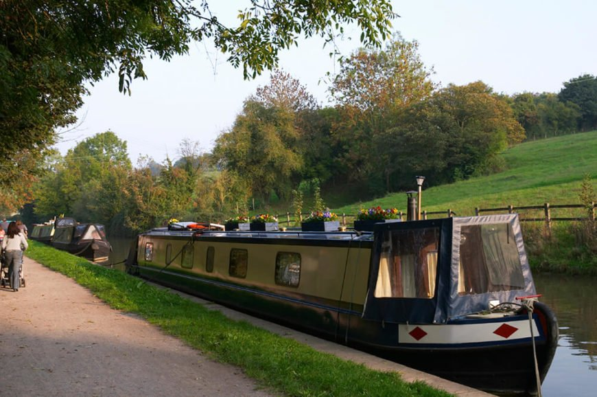 A lengthy houseboat with displays of flowers along the top. This houseboat is moored along a canal in the Netherlands, across from a beautiful meadow.