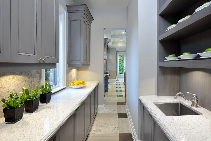 A slim, narrow galley kitchen with tons of storage and a large sink. The light gray cabinetry provides a slight contrast to the white countertops without making the sandy backsplash clash.