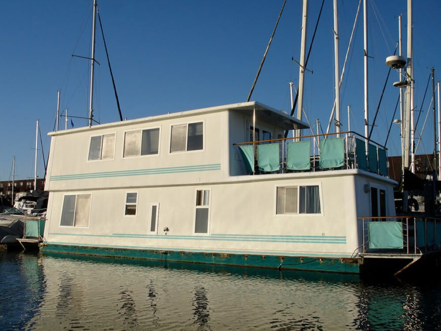 A large moored houseboat designed to be a permanent home. The boat has no side railings, and two small decks on the front and rear of the boat. Like many permanent house boats in North America, this one is moored in a large marina.