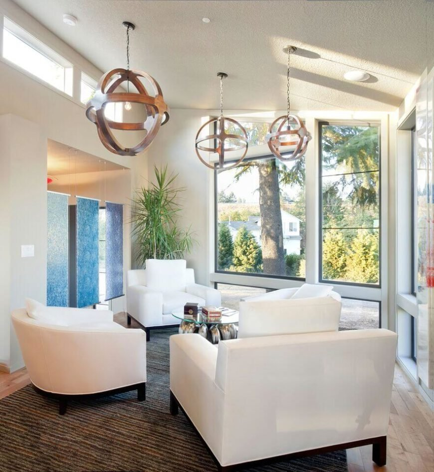 This tall living room is awash in bright tones and unique details, including a trio of wood spherical lights hanging above the set of pristine white club chairs. Two sets of full height windows and blue glass room dividers brighten the entire space.