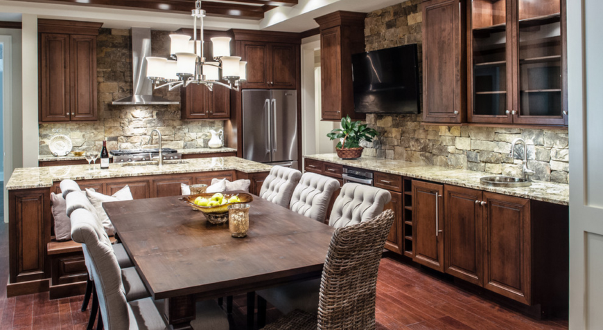 L shape kitchen with hardwood floors and wooden cabinetry along with brick backsplash and marble countertops added by a dine-in table set.