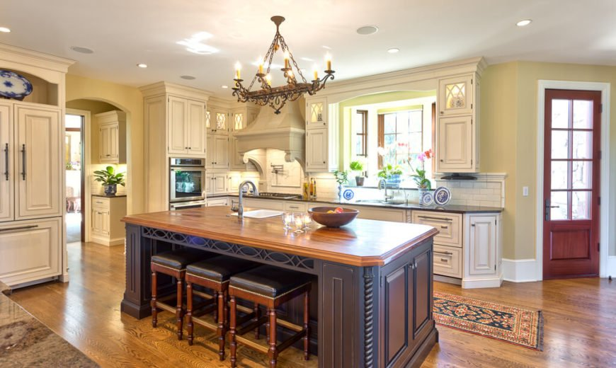 Huge kitchen with white cabinetry and hardwood floors along with a large center island featuring wooden countertop and space for a breakfast bar lighted by recessed lights and chandelier.