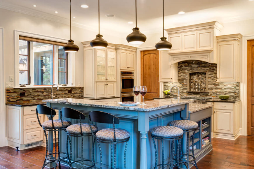 L shape kitchen with stylish camou backsplash and white cabinetry along with a center island featuring marble countertop and a breakfast bar lighted by recessed and pendant lights.