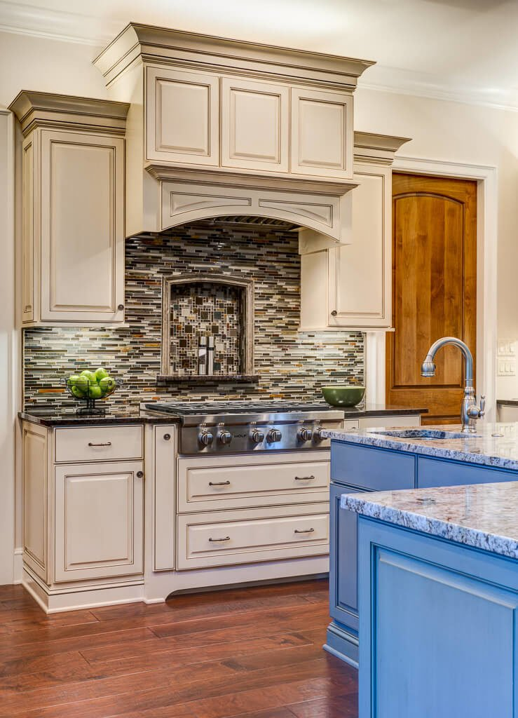 Kitchen with hardwood flooring and stylish camou backsplash along with a center island featuring a marble countertop.