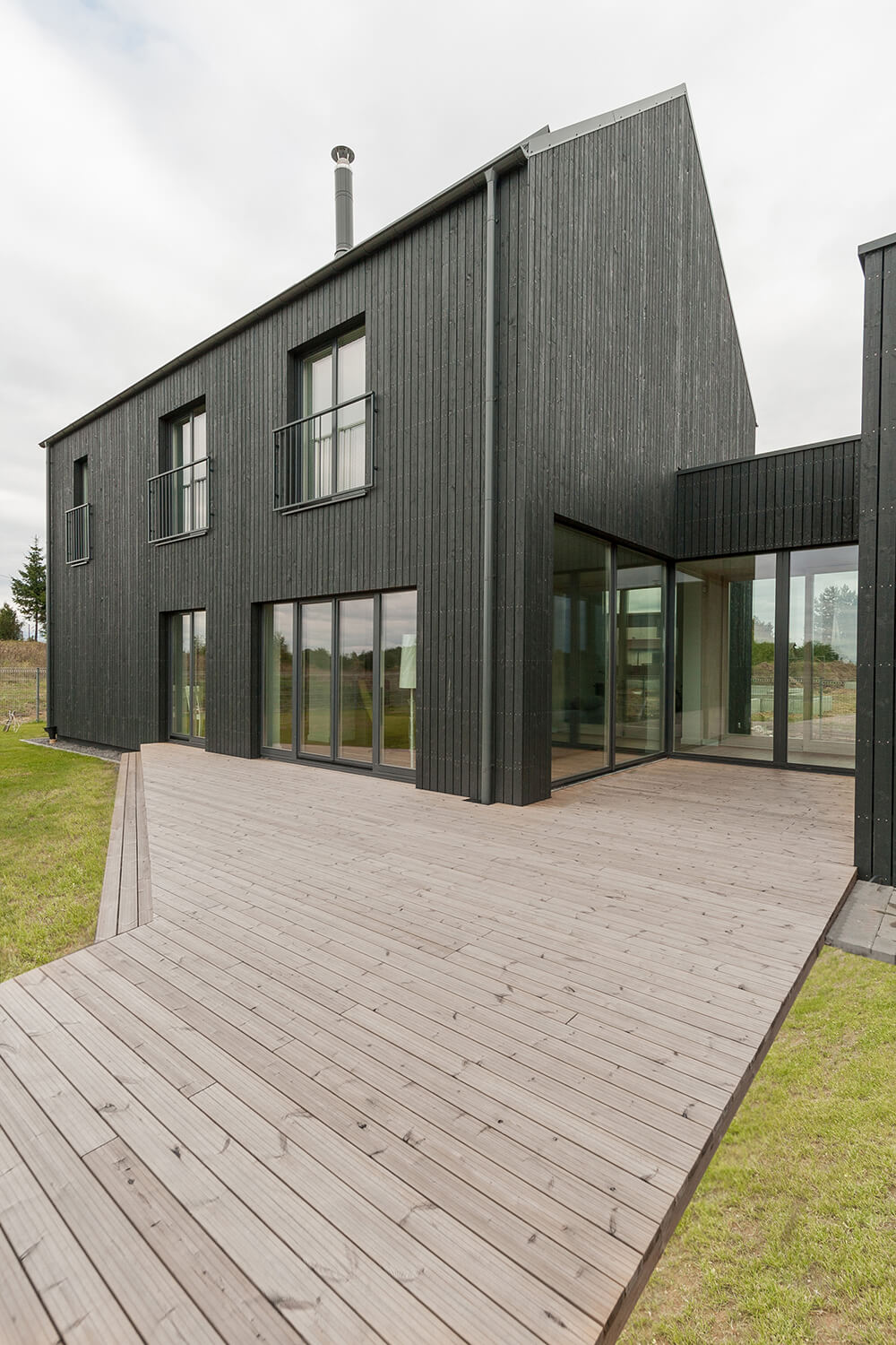 This modern house features a deck leading to the property's grassland.