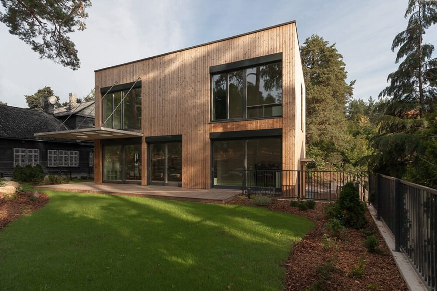 The wooden exterior of this house is designed to blend in with the surrounding old pine trees and hills while still remaining separate from it through the boxy shape of the structure and the inclusion of plenty of large windows.