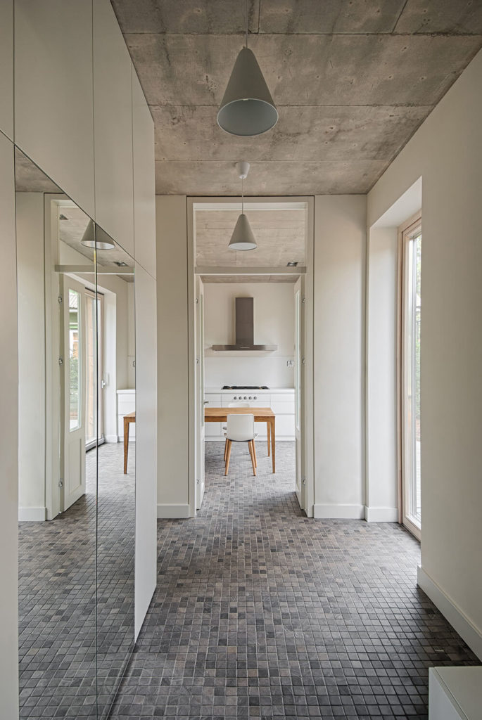 This interior hallway looks into the kitchen. The mirrors help to reflect light into the hall from the sliding door that opens onto the deck. Concrete ceilings are a great choice for regulating temperature and keeping the house cool in the warm months. The gorgeous tile floor offsets the pale walls and ties the pale concrete into the color scheme.