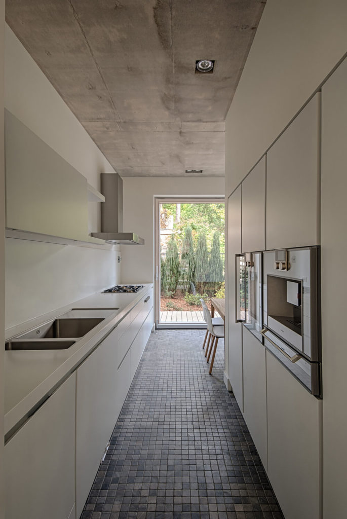 The narrow kitchen continues the pale color palette of the house with the same floors and ceilings. The streamlined minimalist design of the room, with all the low profile cabinets and stainless steel accents continues the simple design of the rest of the house.
