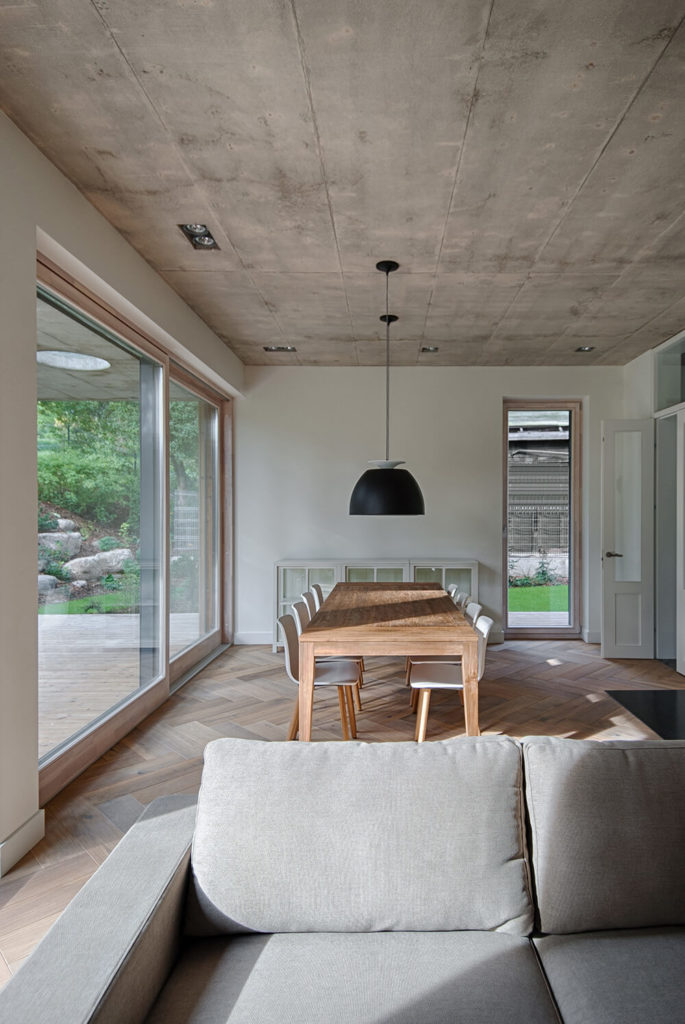 The dining room features a long farm style table with plenty of seating to entertain and a glass paned buffet at the far end of the room. The dining room opens right into the living room as one can see by the couch in the foreground.