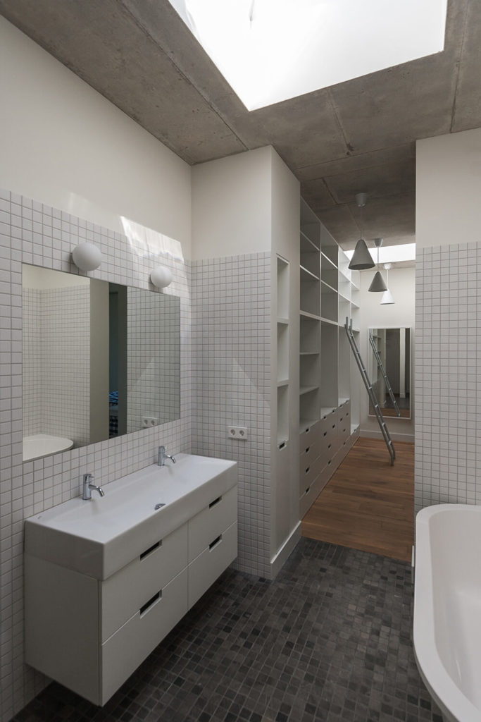 The primary bathroom and walk-in closet are narrow but fully equipped with a double vanity and a soaking tub. A large skylight fully lights the room. White tiles keep the pale color palette of the rest of the house and the tiles from the first floor make another appearance in the bathroom.
