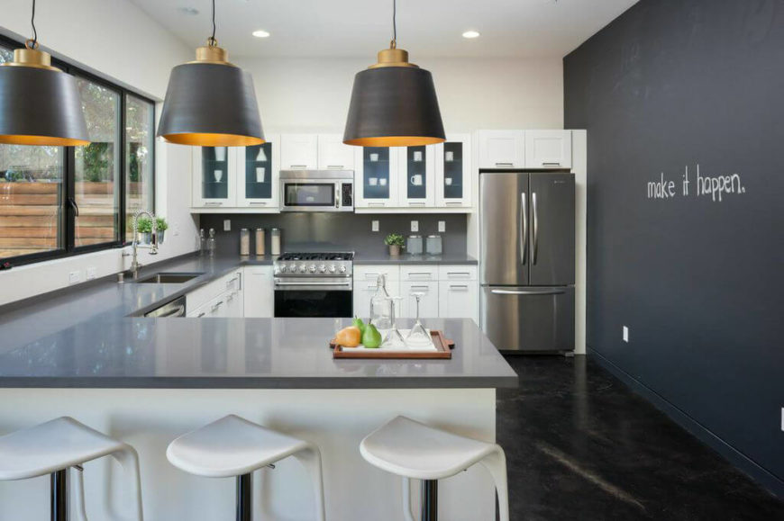 G shape kitchen with white cabinetry and smart appliances along with smooth countertops and a breakfast bar lighted by recessed and pendant lights.