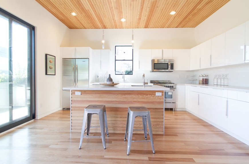 Simple L shape kitchen with white walls and hardwood flooring along with marble countertops and recessed ceiling lights.