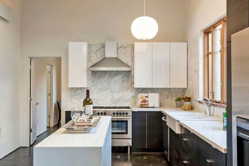 Here's a close look at the kitchen, with white countertops, black cupboards, and a bold marble backsplash that wraps the upper white cabinetry and sink area. A slim white island offers more contrast and helps define the area.
