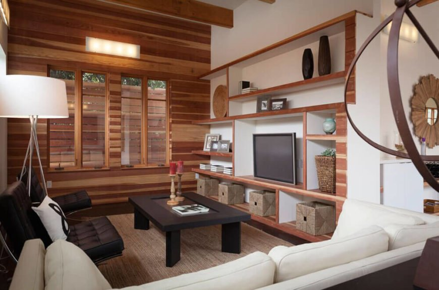 At the far end of the open area, we see the living room decked out in swaths of natural wood and elegant contemporary furniture. A complex set of built-in shelving on the wall provides space for art and storage, while the all-wood feature wall at left continues this element within the home.