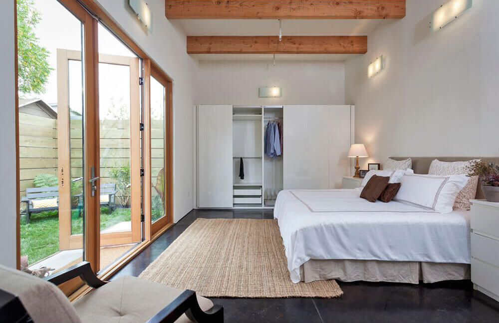 White wall lights surrounded this primary bedroom which features wooden framed glass doors and exposed wood beams. A taupe bed dressed in white bedding sits on a light brown jute carpet over black flooring.