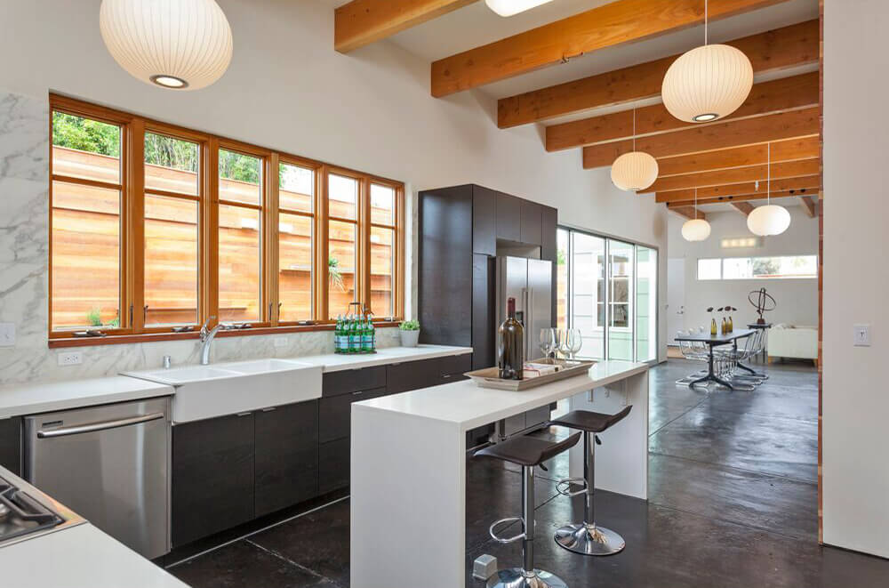 A modish kitchen featuring white countertops and a waterfall style center island lighted by pendant lights set on the ceiling with exposed beams.