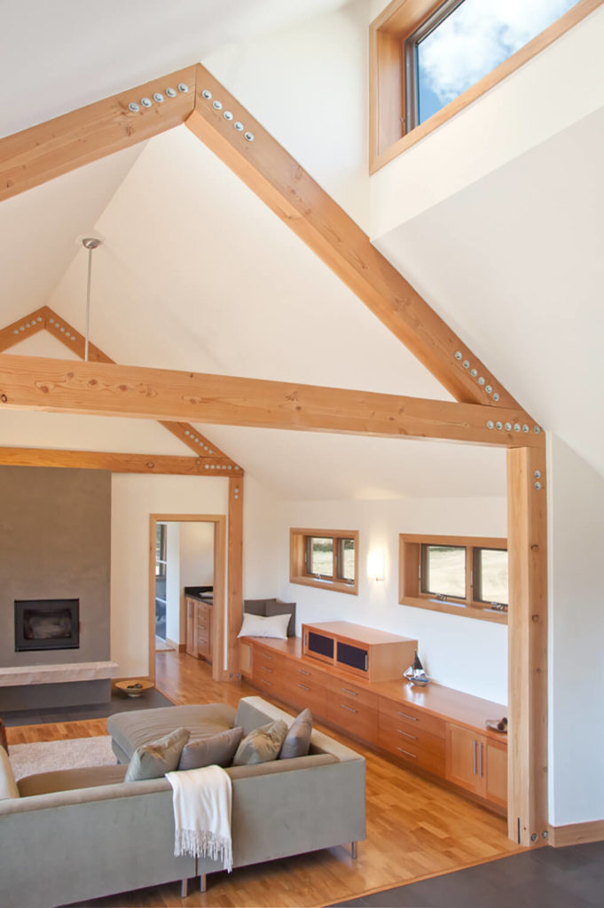 The natural wood used throughout, from the flooring to the cabinetry and window frames, appears in a narrow band of shades, making for a neatly cohesive design.