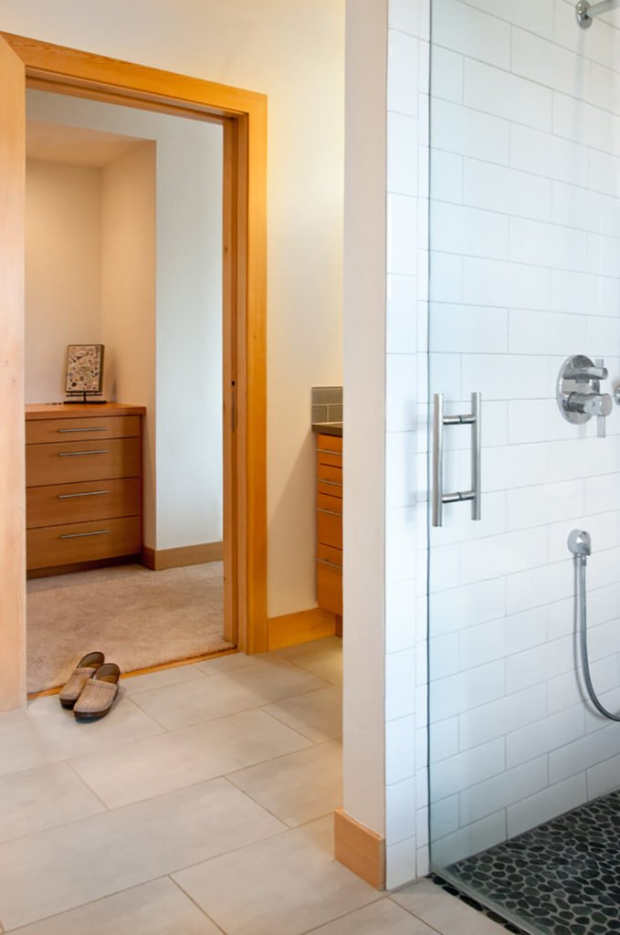 The primary bath suite features a glass enclosed walk-in shower with white tile walls, a change of material while keeping the same color palette used throughout the home as stylistic connective tissue.