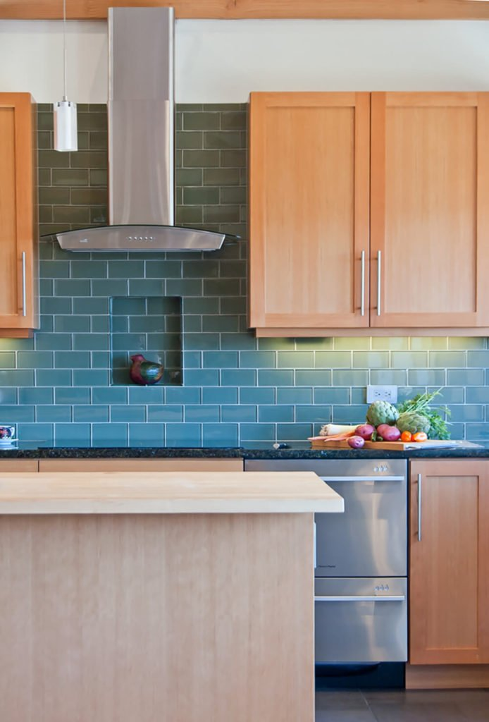 The subway tile backsplash features a wall-cove cutout for display, similar to those found next to the fireplace. Details like this truly enhance the comforting atmosphere of the home.