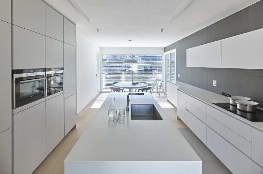 Galley type kitchen with smooth white countertops and cabinetry along with a large center island and smart appliances.