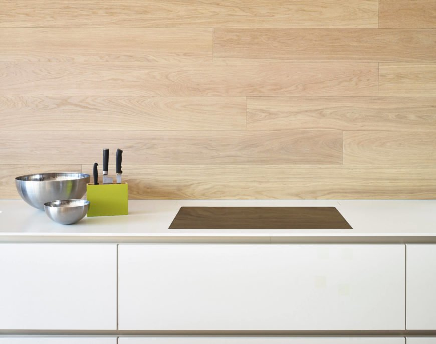 Kitchen showcasing a smooth white countertop and a wooden backsplash.