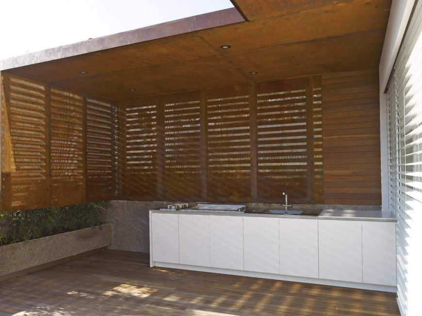 Close up view of the outdoor kitchen on deck featuring a white counter lighted by recessed ceiling lights.
