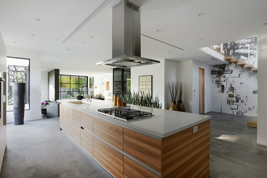 Opposite of the staircase, there is a large kitchen island, complete with a sink and stove. A rich wood grain is wrapped around the outer edge of the island, and also covers the drawers on the inside of the island.