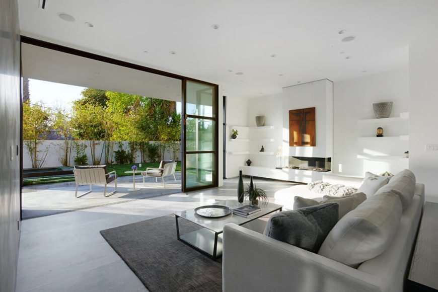 In the living room, you will notice that this space also opens up to a backyard and patio area. The L-shaped couch faces the patio opening, providing a relaxing space to enjoy the natural light and fresh air. Multiple shelving units and a modern fireplace is featured on the adjacent wall.
