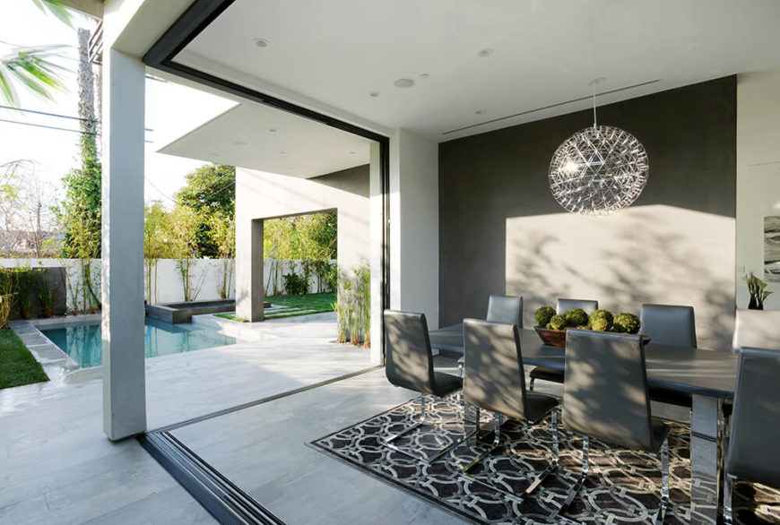 This dining space allows you to enjoy the evening air while still remaining in a comfortable interior setting. A large sliding curtain can be pulled out of the wall to create a barrier for this dining room. Otherwise, it shares an open space with the patio and pool area.