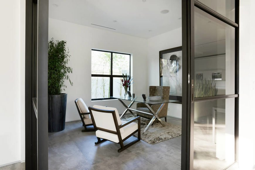 This home also includes an office space, complete with stylish designer chairs and a fashionable modern glass desk. The white and black color scheme make the space both professional and comfortable. A large plush carpet also compliments the surrounding floor.