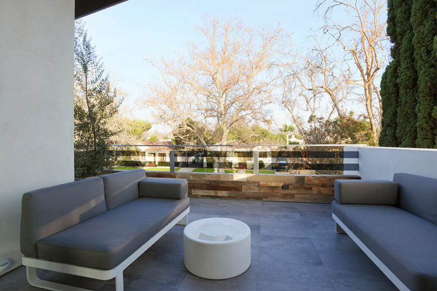 The exterior of this home features a patio space and pool in the backyard, but this upper level deck also includes two couches for lounging in the outside air. The flooring is consistent with that of the interior, and a dark glass railing helps to give the patio space some extra privacy.