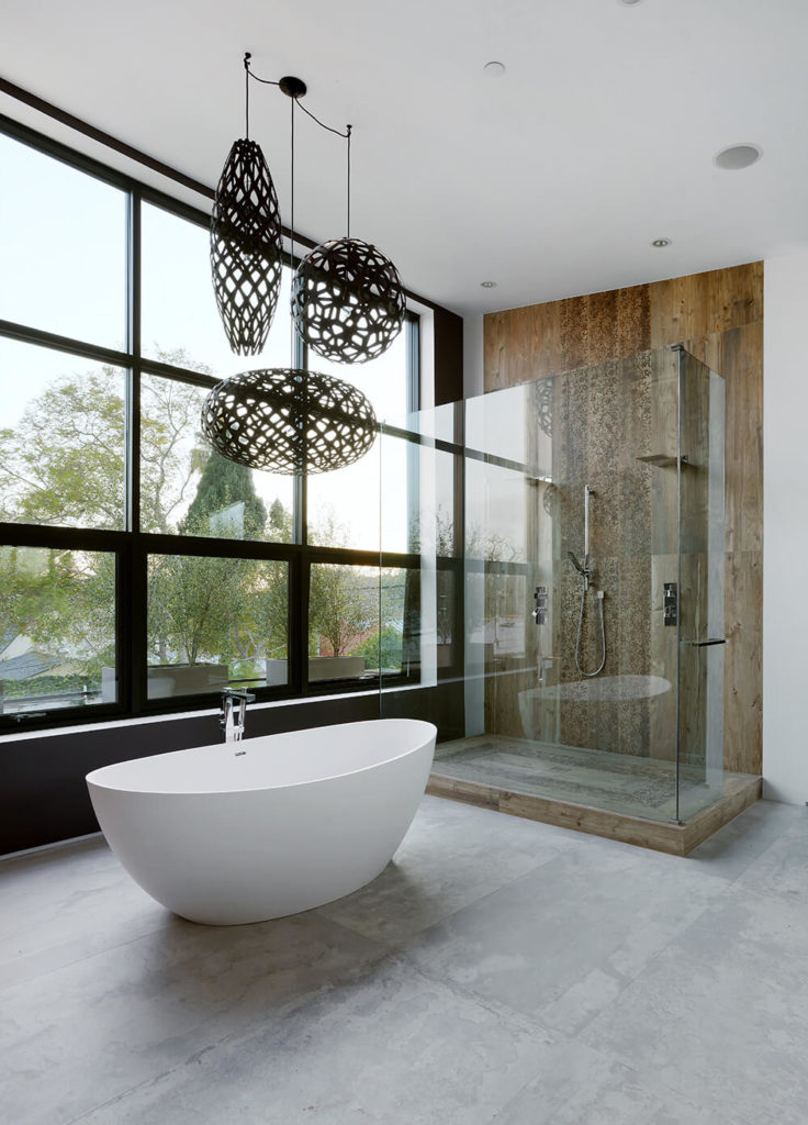 The bathroom space also features a sophisticated soaking tub, set in front of a large wall of windows, providing a view. The walk in shower is encased in glass and features a wood grain interior, contrasting the rest of the bathroom.