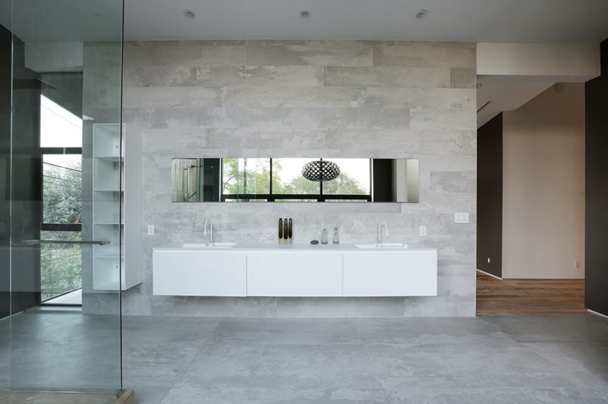 This bathroom space is open and quite spacious. A single counter is mounted to the wall with cabinets featured below. Two sinks allow for two people to wash up at the same time, and a long mirror runs the length of the countertop. The textured tile floor extends up the wall and to the ceiling.