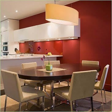 Kitchen with white cabinetry and counters along with red walls lighted by recessed lights, also featuring a dine-in table set.