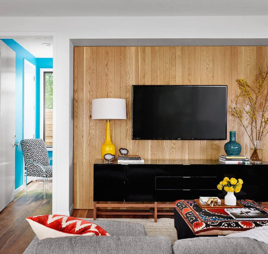The family room features a similar splash of bright natural wood, backing the sleek black entertainment center. In the next room, we can see sky blue walls, another fresh wrinkle in the interior design of this home.