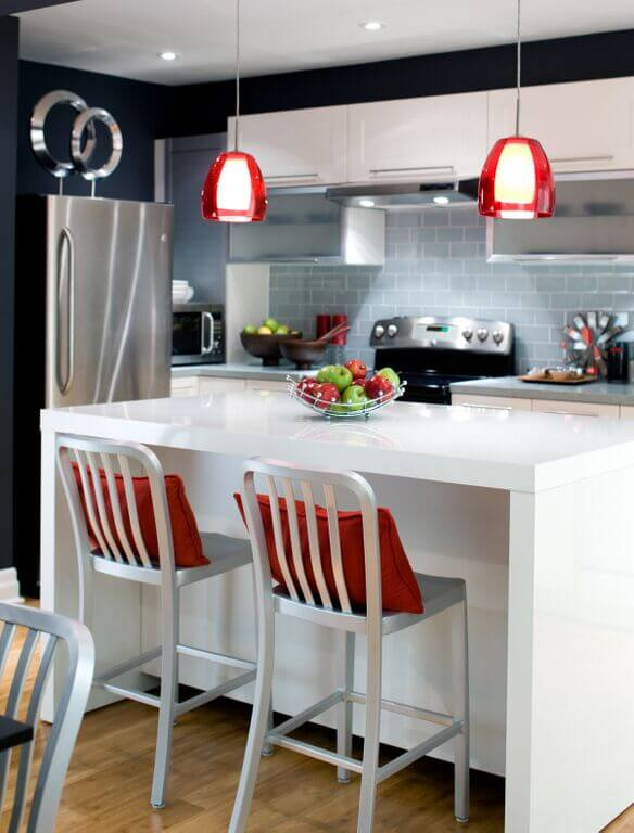 Contemporary kitchen with black walls and tiles backslash along with white cabinetry and small center island featuring a breakfast bar lighted by recessed and pendant lights.