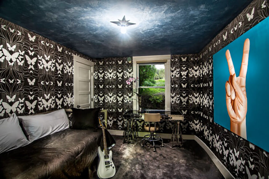 """This cozy home office space features detailed butterfly patterned wallpaper and a large """"peace sign"""" artwork on the wall, surrounding the minimal set of furniture with rich detail."""